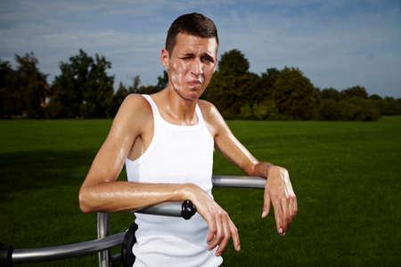 uomo alto: Molto sottile e alto uomo esercita su luogo all'aperto sul parco di fitness pubblico nel periodo estivo.