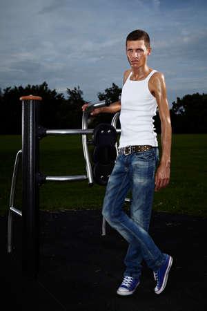 uomo alto: Molto sottile e alto uomo di relax dopo l'allenamento sul luogo all'aperto in parco pubblico di fitness in estate.