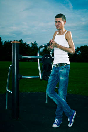 scrawny: Very slim and tall man relaxing after workout on outdoor location on public park fitness in summer time.