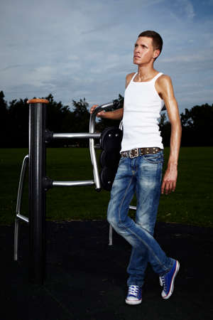 tall man: Very slim and tall man relaxing after workout on outdoor location on public park fitness in summer time.