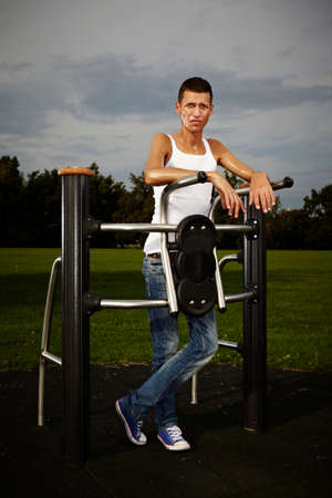 scrawny: Very slim and tall man exercising on outdoor location on public park fitness in summer time.