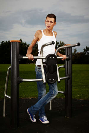 tall man: Very slim and tall man exercising on outdoor location on public park fitness in summer time.