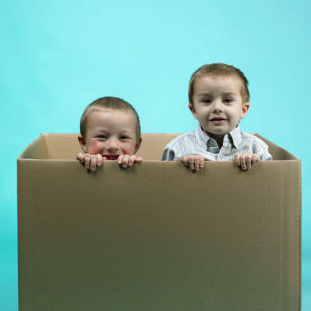 Children in studio portrait posing in large paper box