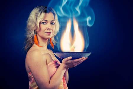 esoterismo: Mujer de alma esotérica sosteniendo una bandeja llena de llamas que describen llamas internas del alma