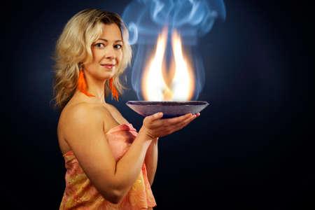 esoterismo: Mujer de alma esot�rica sosteniendo una bandeja llena de llamas que describen llamas internas del alma