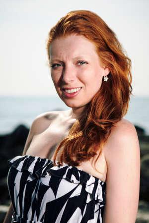 italian sea: Nice redhead young lady posing outdoor near stone pier on Italian sea beach. Stock Photo