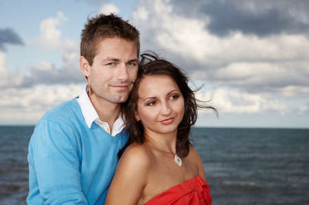 baffle: Young couple posing by the sea on stone baffle pier in Italian tourist resort Caorle in various dresses.