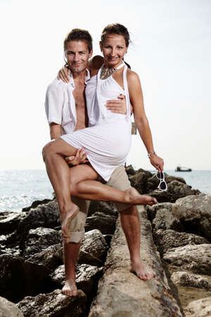 baffle: Couple on the baffle pier posing fo figure portraits on beach in Italy in summer white dresses.