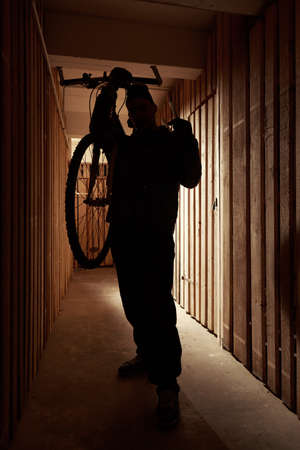 thieving: Man in mask during robbery in house basement cellar stealing bicycle.