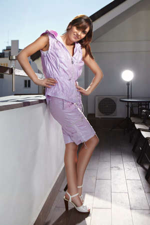 fashion photos: Young brunette woman posing on house balcony  for fashion photos in several clothes and dresses. Stock Photo