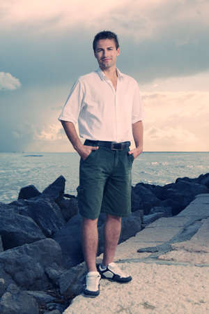 baffle: Young male model posing by the sea on baffle pier for portrait and figure photos in Italian city Caorle