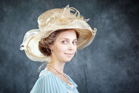 sedition: Lady of old times in ancient secession-style apparel and hat posing in studio for retro portraits.