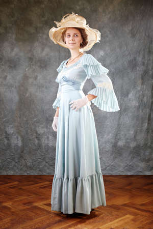 century: Lady of old times in ancient secession-style apparel and hat posing in studio for retro portraits.