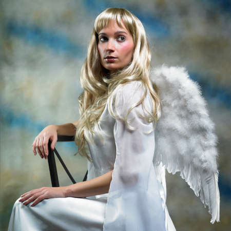 angel wing: Blonde angel in studio - lady posing with angel wings