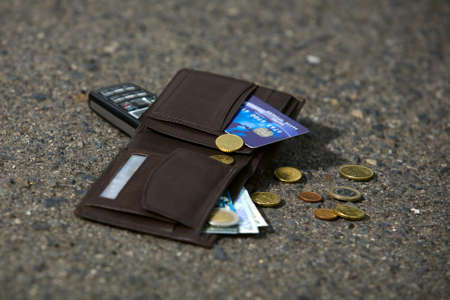 id theft: Lost man wallet and mobile at the park sidewalk Stock Photo