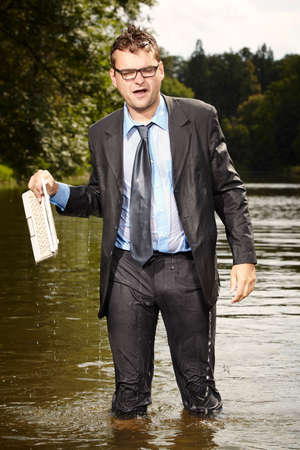 Crazy man in suit saving his notebook from water