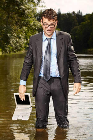 Crazy businessman in suit trying to save notebook from water