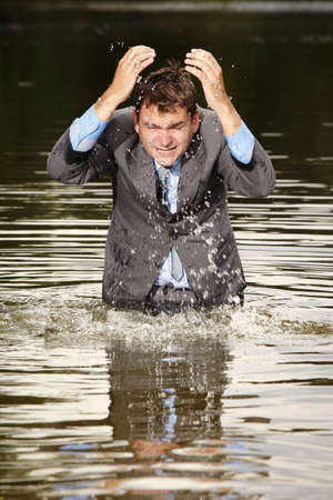 Crazy businessman in suit deep in water Stock Photo