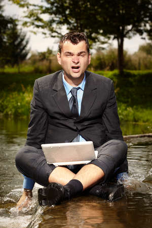 Crazy businessman in suit relaxing after burning out in water