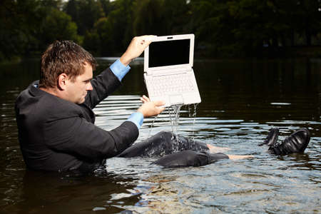 freak out: Crazy businessman in suit pouring water out of laptop
