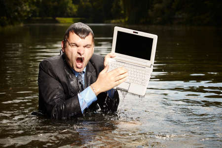 freak out: Crazy businessman in suit saving notebook from water
