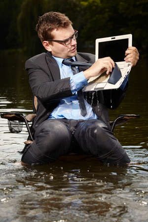 freak out: Crazy businessman in suit cleaning computer in river