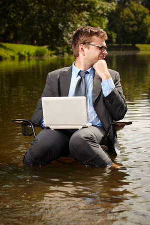 Crazy businessman in suit sitting on chair in river