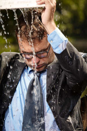 Crazy businessman in suit pouring out water from laptop