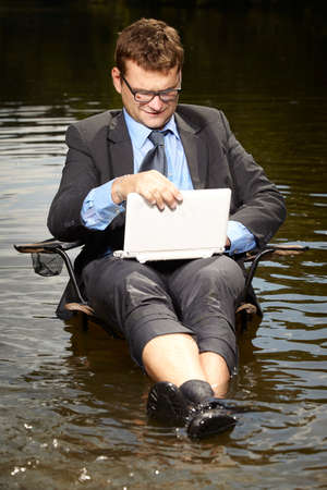 Crazy businessman in suit relaxing in river after burning out