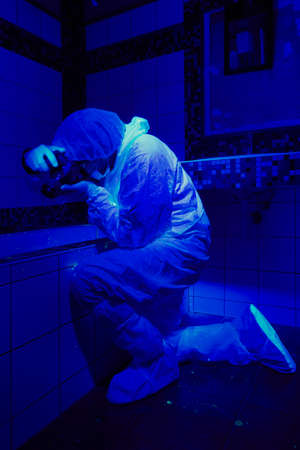 theft proof: Criminologist on place of bloody crime under UV light Stock Photo