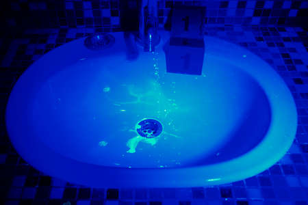 theft proof: Developing of evidence in wash basin under UV light Stock Photo