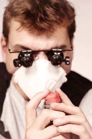 Bomb maker filling plastic explosive to a tube