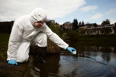protective suit: Man in overall protective suit collecting samples of water