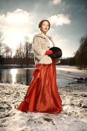 Nice woman in fur coat and red apparel posing in winter park