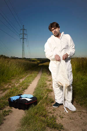 Police technician dressing disposable overall and protective equipment