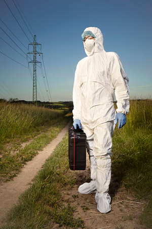 Criminologist technician in disposable overall and protective equipment