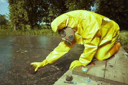 Scientist in chemical protective suit collecting samples of water contamination Stock Photo