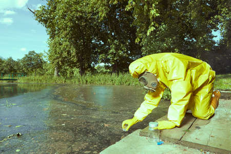 Technician in chemical protective suit collecting samples of water contamination