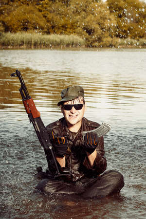bathe: Funny soldier in uniform sitting in lake with assault rifle