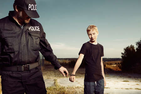 pickpocket: Police man catching youth pickpocket to handcuffs