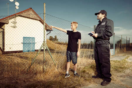 Police man asking youth thief outdoor Stock Photo
