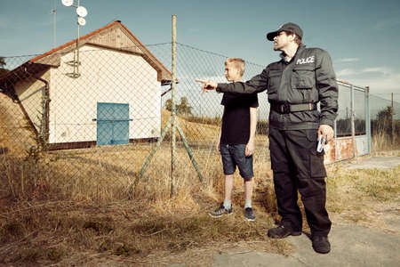 Police man asking youth teenager outdoor