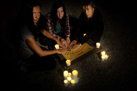 Mujer brujas comunicándose con fantasmas a través de tablero espiritual Foto de archivo - 83751088