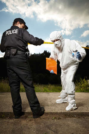 Police man on place of crime with criminologist technician Stock Photo