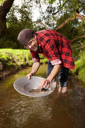 prospector: El prospector afortunado contemporáneo encontró la porción del oro en el arroyo al pisar la arena Foto de archivo