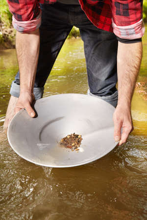 Contemporary lucky prospector found lot of gold in creek when panning sand 版權商用圖片 - 84256426