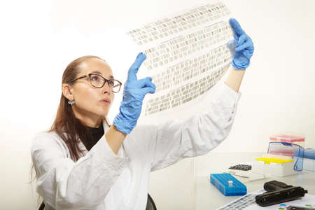 Criminologist lab technician reading film with analysed DNA Stock Photo