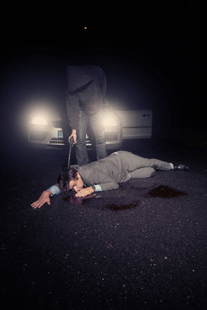 felonious: Masked murderer shooting man in suit in front of car on route Stock Photo