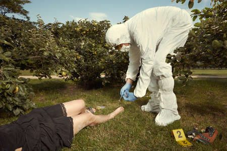 Young blonde woman in black apparel found in park - investigation Stock Photo
