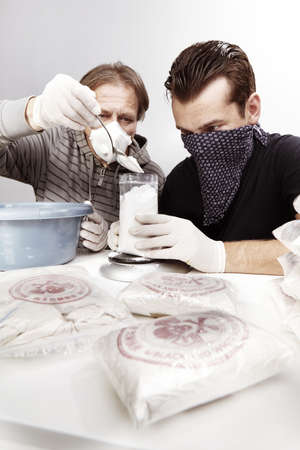 Two dealers packing lot of drugs for distribution
